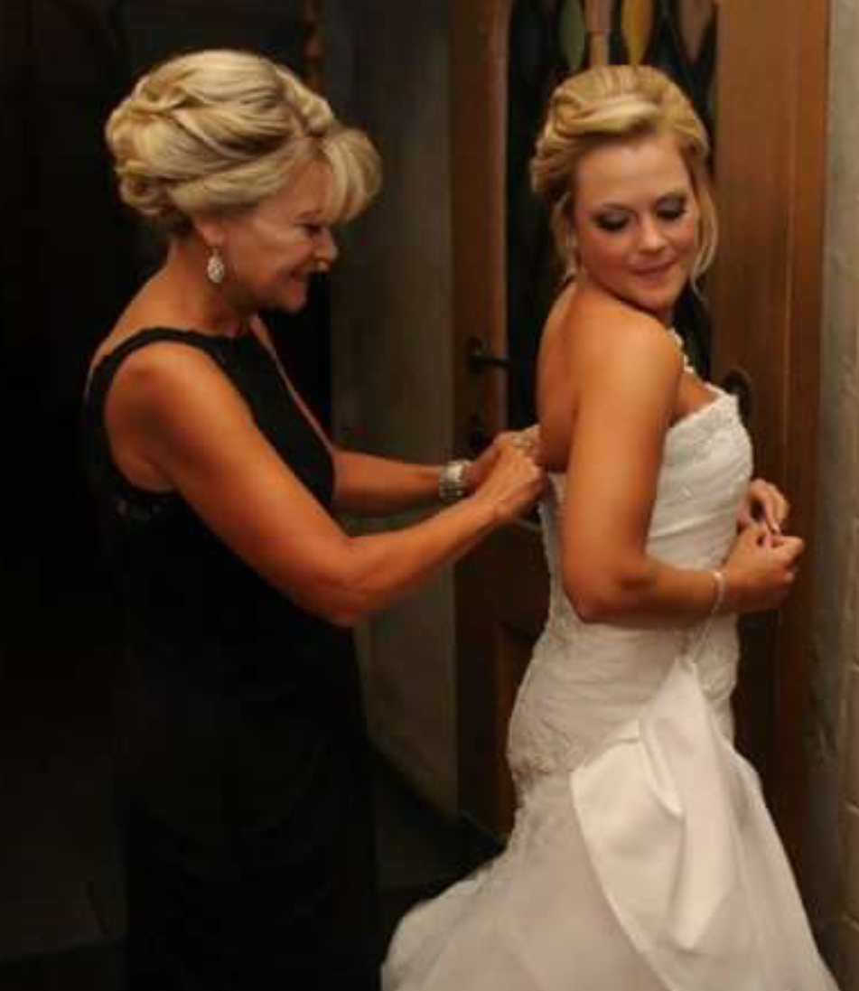 With a little help, the lovely bride is almost ready for her special entrance.